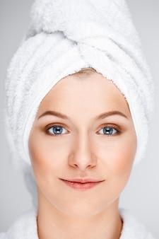 Довольно блондинка женщина обернуть банное полотенце на мокрые волосы