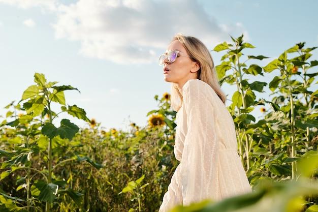 들판의 카메라 앞에 큰 꽃들 사이에 서 있는 동안 해바라기 기름 한 병을 들고 흰 드레스를 입은 꽤 금발의 젊은 여성