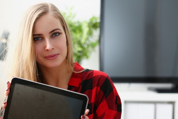 Pretty blond young woman hold laptop in arms sit on sofa