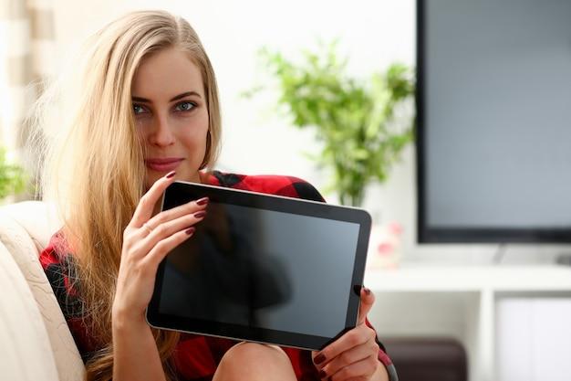 Довольно белокурая молодая женщина держит ноутбук в руках, сидя на диване