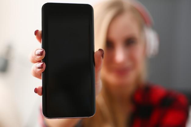 Довольно белокурая молодая женщина держит телефон в руке крупным планом