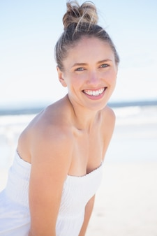 Pretty blonde on the beach smiling at camera