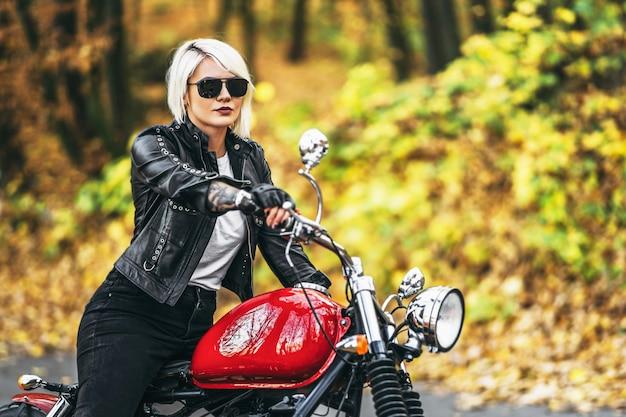 Довольно блондинка байкер девушка в солнцезащитных очках с красным мотоциклом на дороге в лесу