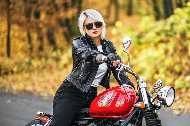 Pretty blonde biker girl sitting near red motorcycle on the road in the forest