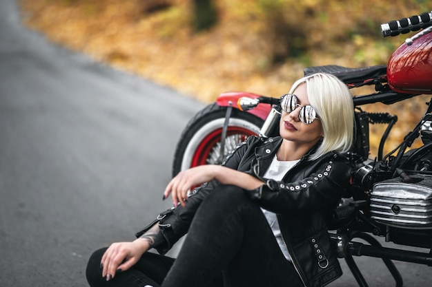 Pretty blonde biker girl in sunglasses sitting near red motorcycle on the road in the forest