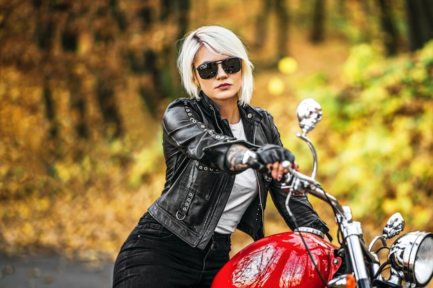 Pretty blonde biker girl in sunglasses with red motorcycle on the road in the forest