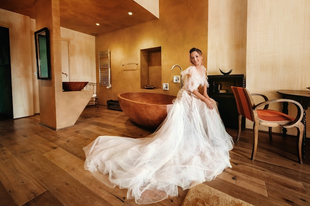 Nicea와 예쁜 금발의 신부 웨딩 드레스에 즐거운 기능을 가진 아름다운 신부가 방의 내부에서 포즈를 취합니다. 프로방스에서 신부 초상화입니다. 프랑스.