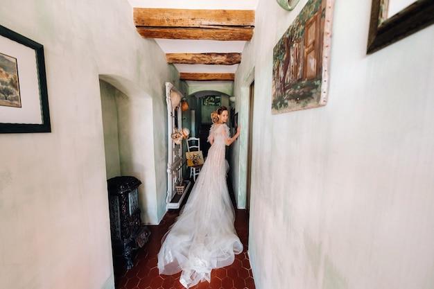 Nicea와 예쁜 금발의 신부 웨딩 드레스에 즐거운 기능을 가진 아름다운 신부가 방의 내부에서 포즈를 취합니다.