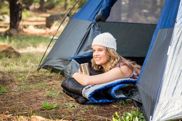 笑顔とテントで横たわっているかなりブロンドのキャンピングカー