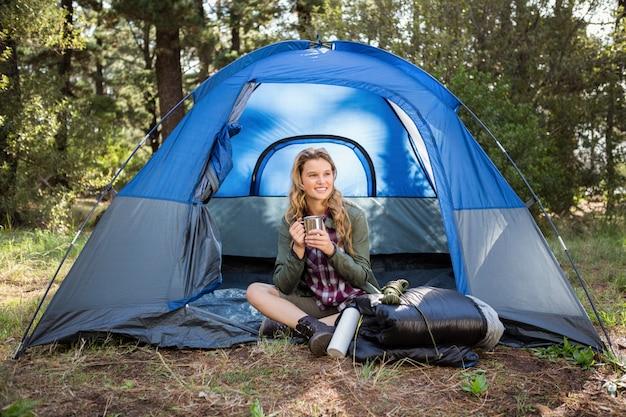 笑顔とテントで座っているかなりブロンドのキャンピングカー