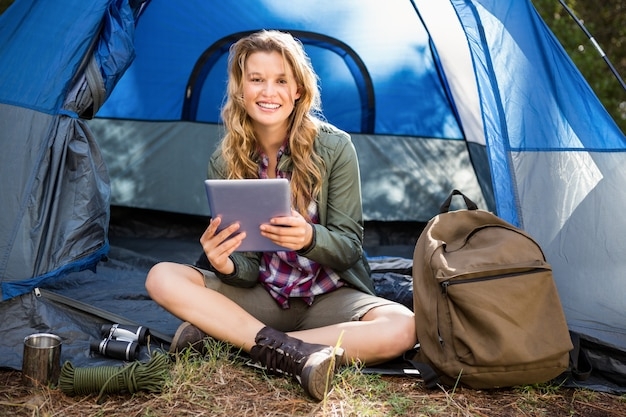 タブレットを使用してテントに座っているかなりブロンドのキャンピングカー