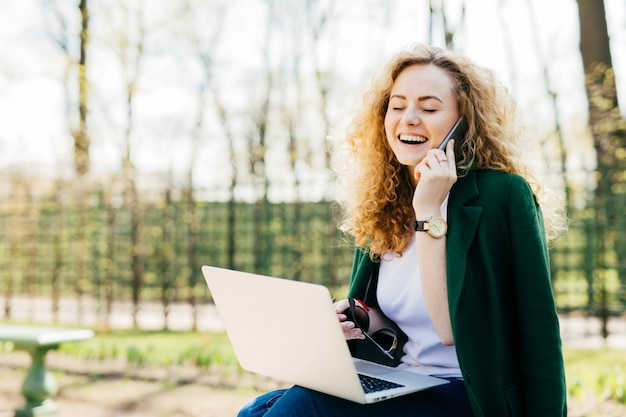 Pretty blonde female wearing green jacket sitting outdoors in park speaking over smartphone closing her eyes.