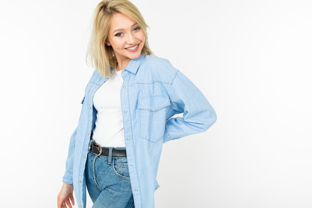 Pretty blonde girl in blue jeans shirt smiling cute on a white studio background
