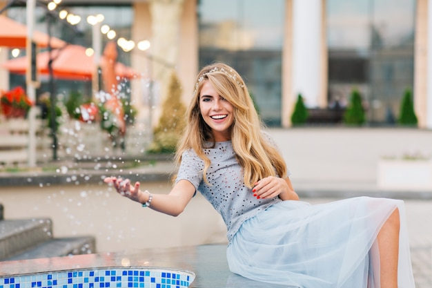 Pretty blonde girl in blue tulle skirt having fun on terrace background. she splashing water and smiling to camera.