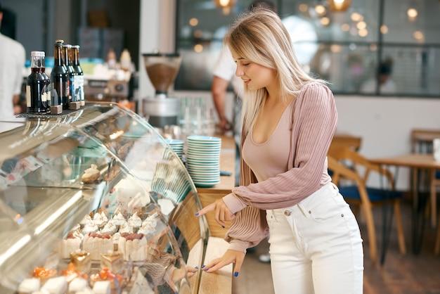 Pretty blonde girl choosing dessert from glass showcase in bakery shop.