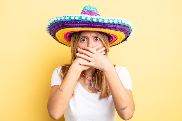 Довольно блондинка закрыла рот руками с потрясенным. концепция мексиканской шляпы