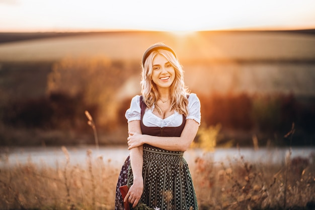 Pretty blonde girl in dirndl, standing outdoors in the field, holding bouquet of a field flowers.