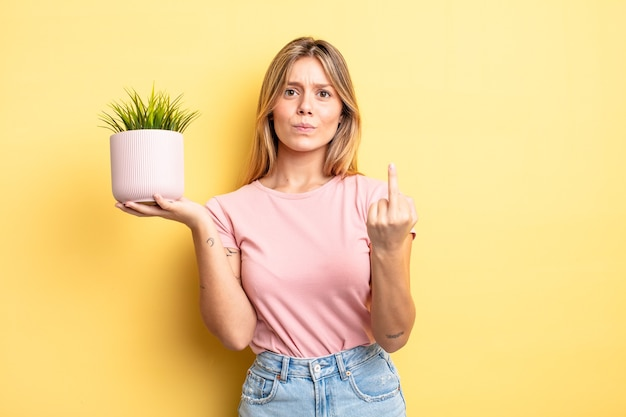 Pretty blonde girl feeling angry, annoyed, rebellious and aggressive. houseplant concept