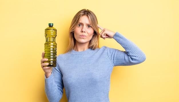 Симпатичная блондинка смущена и озадачена, показывая, что вы сошли с ума. концепция оливкового масла