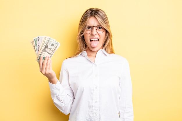 Довольно блондинка чувствует отвращение и раздражение и язык. доллар банкноты концепция