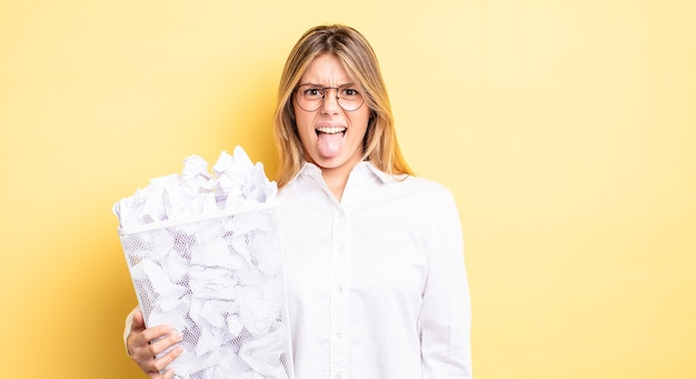 Довольно блондинка чувствует отвращение и раздражение и язык. бумажные шары мусор концепция