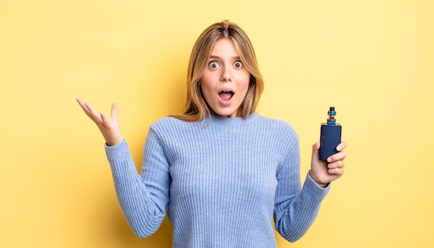 Pretty blonde girl feeling extremely shocked and surprised. smoke vaporizer concept
