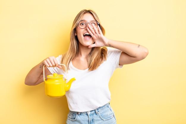 Довольно белокурая девушка чувствует себя счастливой, громко кричит, прижав руки ко рту. концепция чайника