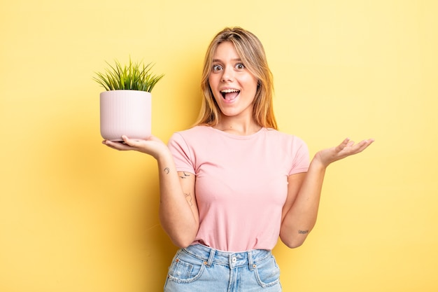 Довольно белокурая девушка чувствует себя счастливой, удивленной, осознав решение или идею. концепция комнатного растения