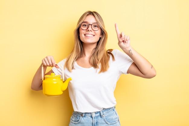 Симпатичная белокурая девушка чувствует себя счастливым и взволнованным гением после реализации идеи. концепция чайника