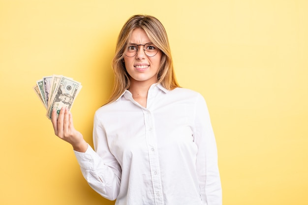 Pretty blonde girl feeling puzzled and confused. dollar banknotes concept