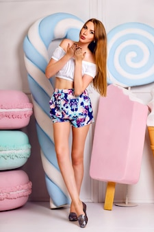 Pretty blonde girl having fun near gigant sweetness, lollipops ,ice-cream, macaroons, cute trendy feminine outfit, long hairs, pastel colors, positive vibe.