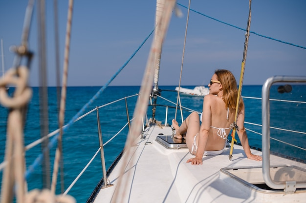 Pretty blonde girl is wearing fashion swimsuit doing summer trip on a yacht.