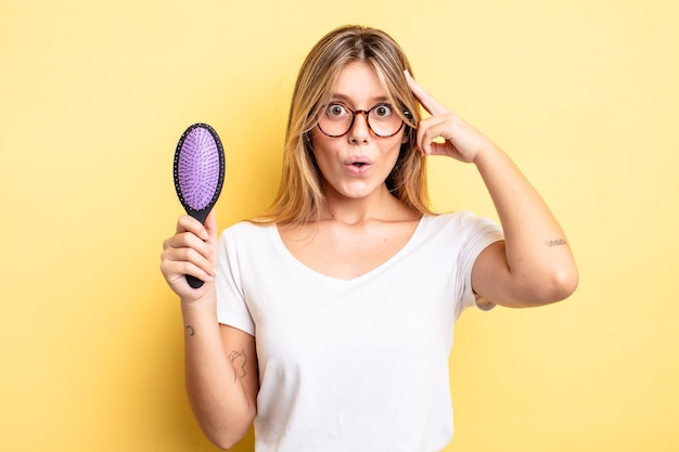 Pretty blonde girl looking surprised, realizing a new thought, idea or concept. hair brush concept