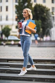 Modello di ragazza abbastanza bionda sta andando alle lezioni di lavoro attraverso il citycentre tenendo il computer del caffè notebook tra le mani al mattino