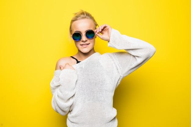 Bella ragazza bionda in maglione bianco moderno in occhiali da sole blu brillanti è in posa su giallo