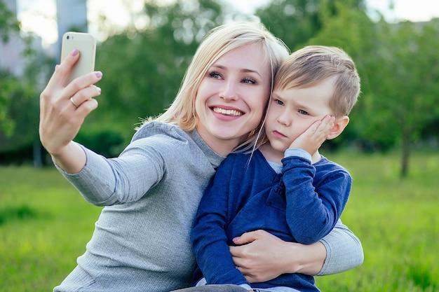 きれいなブロンドの女の子(母)とかわいい息子は、緑の草や木々を背景に公園で電話で自分撮りをします
