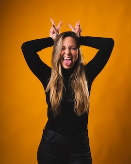 Pretty blonde girl placing her hands over her head while sticking out her tongue in a funny and smiling way wearing a black shirt and pants