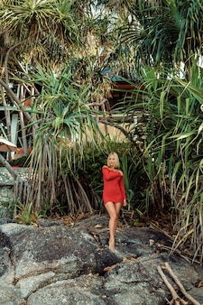 Pretty blonde girl in a short red dress stands on stones in a sexy pose among trees in the jungle near the hotel. phuket. thailand. tourism and travel