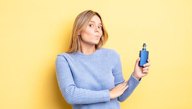 肩をすくめる、混乱して不確かな感じのかわいいブロンドの女の子。煙気化器の概念