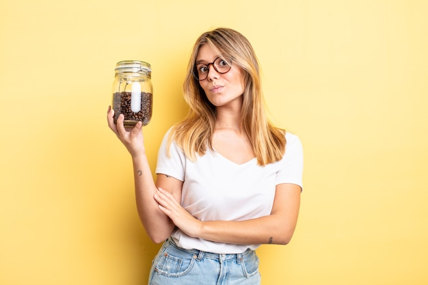 Pretty blonde girl shrugging, feeling confused and uncertain. coffee beans concept