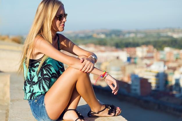 Довольно блондинка девочка, сидящая на крыше.