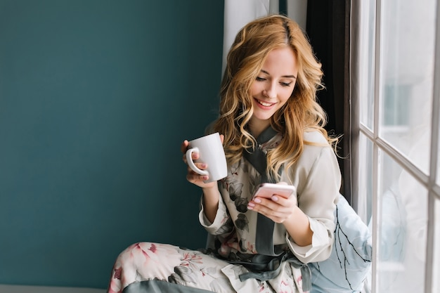 Довольно белокурая девушка сидит на подоконнике с чашкой кофе, чая и смартфоном в руках. у нее длинные светлые волнистые волосы, она улыбается и смотрит в свой телефон. в красивой шелковой пижаме.