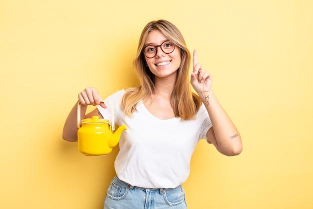 미소하고 친절하고 번호 하나를 보여주는 예쁜 금발 소녀. 주전자 개념