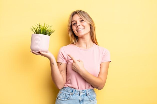 元気に笑って、幸せを感じて、横を指しているかわいいブロンドの女の子。観葉植物の概念
