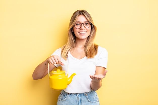 Довольно блондинка девушка счастливо улыбается с дружелюбными и предлагает и показывает концепцию. концепция чайника