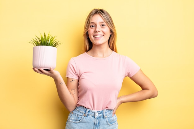 Pretty blonde girl smiling happily with a hand on hip and confident. houseplant concept