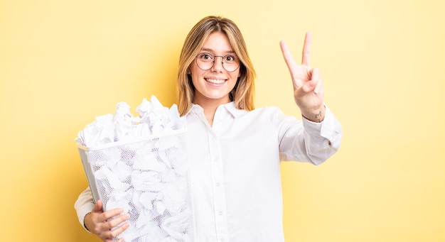 Pretty blonde girl smiling and looking happy, gesturing victory or peace. paper balls trash concept