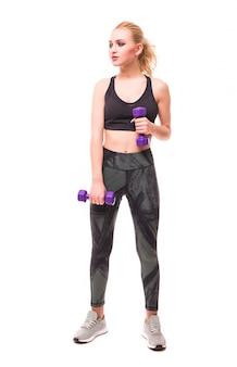 La ragazza bionda graziosa in abiti sportivi lavora al suo corpo