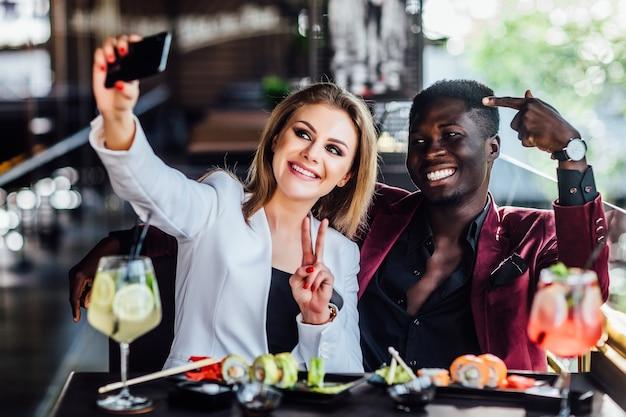 寿司とモヒートで携帯電話で写真を撮るかわいいブロンドの女の子。 cheneseは食べる、友達のカップル。