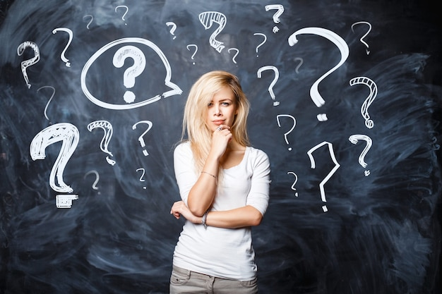 Pretty blonde girl in a white t-shirt asks herself a question on a black background. woman thinks with question marks on chalk board.
